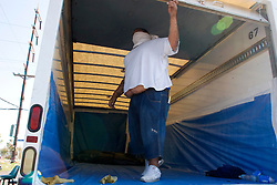 08 Sept 2005. New Orleans, Louisiana. Hurricane Katrina aftermath.<br /> Corpses are finally retrieved from Methodist hospital  in East New Orleans and are loaded into the back of an unrefrigerated truck by private contractors with little to no protection. 8 corpses were already in the truck and another 5 were added. The contractor wears a T-shirt as a face mask. The stench was almost unbearable.<br /> Photo; ©Charlie Varley/varleypix.com