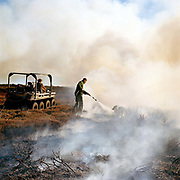 Gamekeeper, Charlie Woof, puts out the fire with water after heather burning, Bransdale, North York Moors, North Yorkshire, UK.  Heather is burnt to regenerate it, the more patches there are on the moor the better it is, producing more habitat for the grouse, and that has a knock on effect for the wader population as well.