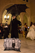 A man with ndertakers hat and umbrella, and cutouts of children drawn in the style of Edward Gorey, the illustrator for whom this year's ball was named.