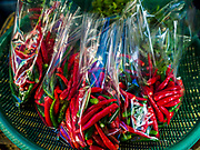 20 JUNE 2018 - BANGKOK, THAILAND:  Chilies in plastic bags at Makkasan Market, a small local market in central Bangkok. Officials in Thailand are wrestling with Thais use of plastic bags. The issue became a public one in early June when a whale in Thai waters died after ingesting 18 pounds of plastic. In a recent report, Ocean Conservancy claimed that Thailand, China, Indonesia, the Philippines, and Vietnam were responsible for as much as 60 percent of the plastic waste in the world's oceans.      PHOTO BY JACK KURTZ
