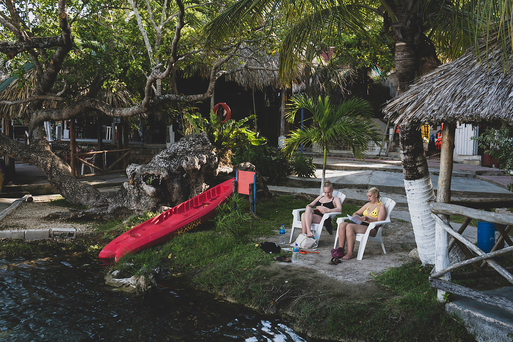 Bacalar, Mexico - June 4, 2021: Eva Rowland and Rosie Galleway, twenty-year-old travelers from England, photographed at Cenote Azul relaxaing and studying Spanish.