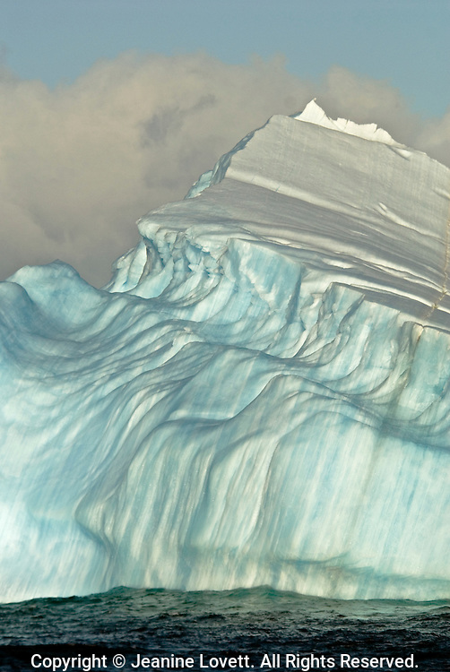 One iceberg that unusual shape was caused by being underwater. At some point this large iceberg has flipped over..