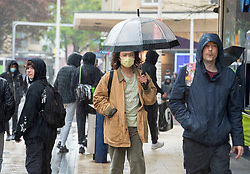© Licensed to London News Pictures; 03/05/2021; Bristol, UK. People cope with wet and windy weather in Bristol's Broadmead shopping centre for a washout on the early May bank holiday. Photo credit: Simon Chapman/LNP.