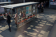 The shadows of commuters in a queue stretching beyond a bus stop shelter at Waterloo, central London.
