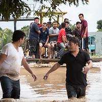 Men leaving a flooded area of La Lima after hurricanes Eta and Iota.