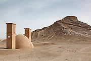 Wind towers (Badgir) next to a building which acts as a refrigerator to store food and Zoroastrian Tower of Silence (Dakhmeh). Yazd, Iran 2007