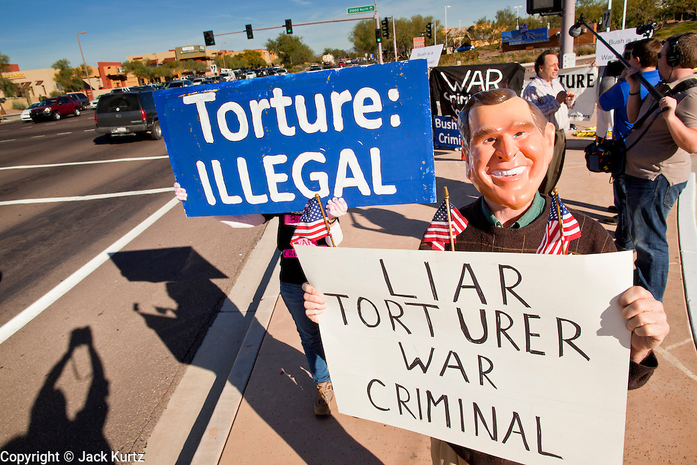 """09 DECEMBER 2010 - PHOENIX, AZ: VICTOR ARONOW, from Tempe, wears a George W. Bush mask while protesting in front of the Barnes & Noble Bookstore in Phoenix, AZ, Thursday, Dec. 9. More than 2,000 people lined up starting at 5AM to get copies of the former President's book, """"Decision Points."""" A handful of protesters demonstrated against President Bush near the bookstore, calling him a """"war criminal.""""   PHOTO BY JACK KURTZ"""