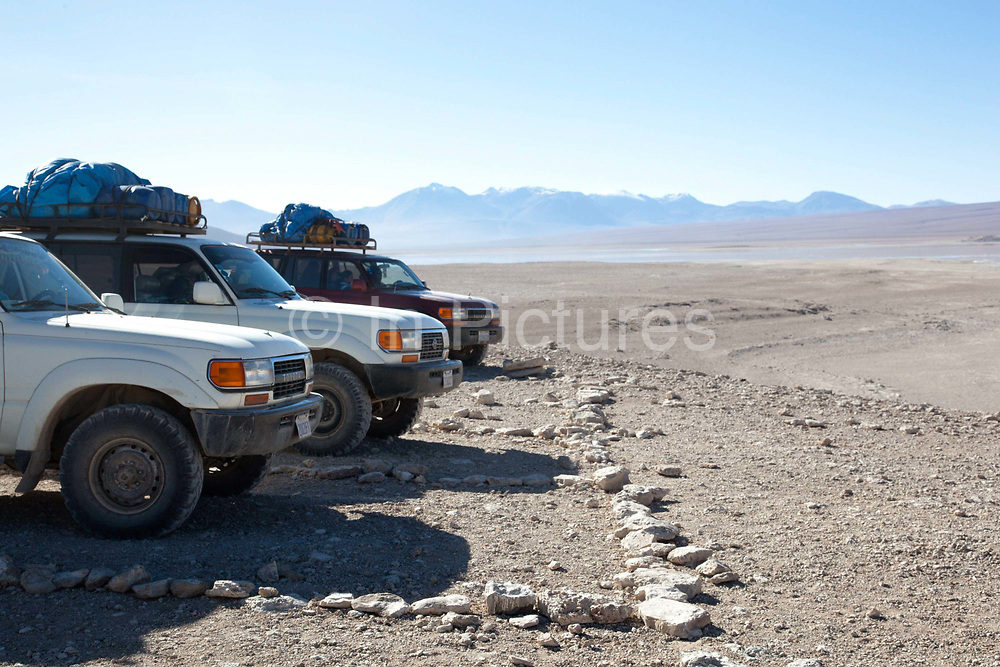 4 x 4's lined up in the desert. Salar Uyuni salt flats and Eduardo Avaroa national park, south western Bolivia