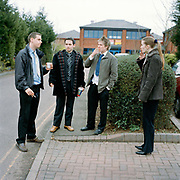Chris Somers, left, Andrew Allen, second from left and colleagues take  a smoke break . This scene must be a familiar sight in car parks on industrial estate around the UK especially since smoking was banned inside public spaces. The dress code is similar for all the workers it seems to the point where it could be considered  as a self imposed uniform. From the series Desk Job, a project which explores globalisation through office life around the World.