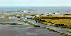 12 june 2010. Wetlands of Plaquemines Parish, South Louisiana. <br /> Vanishing wetlands. Where once there was land, there is only the mere outline of old canals and channels, many dug by oil companies to pump their product ashore with little regard to the effects the chopping up of the wetlands would have. Chronic erosion of the land, a football pitch every 50 minutes, greatly reduced protection from hurricanes and impending BP oil slicks is the direct result of mismanagement and utter disregard for the environment. The army corps of engineers and the oil companies, together with inept government have a great deal to answer for. <br /> View from a blackhawk helicopter flown by airmen of the Nebraska Air National Guard over southern Louisiana as they assist in the dumping of sand bags onto barrier islands in a vain attempt to prevent BP oil from getting into the inner  wetlands. As valiant as their efforts are, the dumping of sand bags may well prove to be a complete waste of manpower, resources and money. Meanwhile, the mighty Mississippi river runs straight out to sea nearby, her valuable land building sediment carried far out into deep ocean as the region struggles to find a way to reverse the disastrous effects of man's inteferance with her flow. <br /> Photo credit; Charlie Varley/varleypix.com