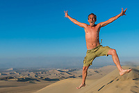 one man jumping in the desert in the peruvian coast at Ica Peru