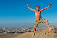 one man jumping in the desert in the peruvian coast at Ica Peru