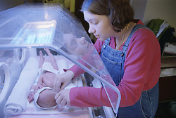 Mother preparing new born baby son for tube feed in Phototherapy machine,