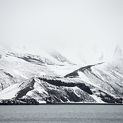 Snow covers the dark volcanic rock of Whalers Bay on Deception Island. Deception Island, in the South Shetland Islands, is a caldera of a volcano and is comprised of volcanic rock.