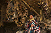 Ecuadorian Chagra (cowboy) in Tack Room<br /> Hacienda del Vallle  (Ranch)<br /> base of Cotopaxi Volcano<br /> Andes<br /> ECUADOR.  South America