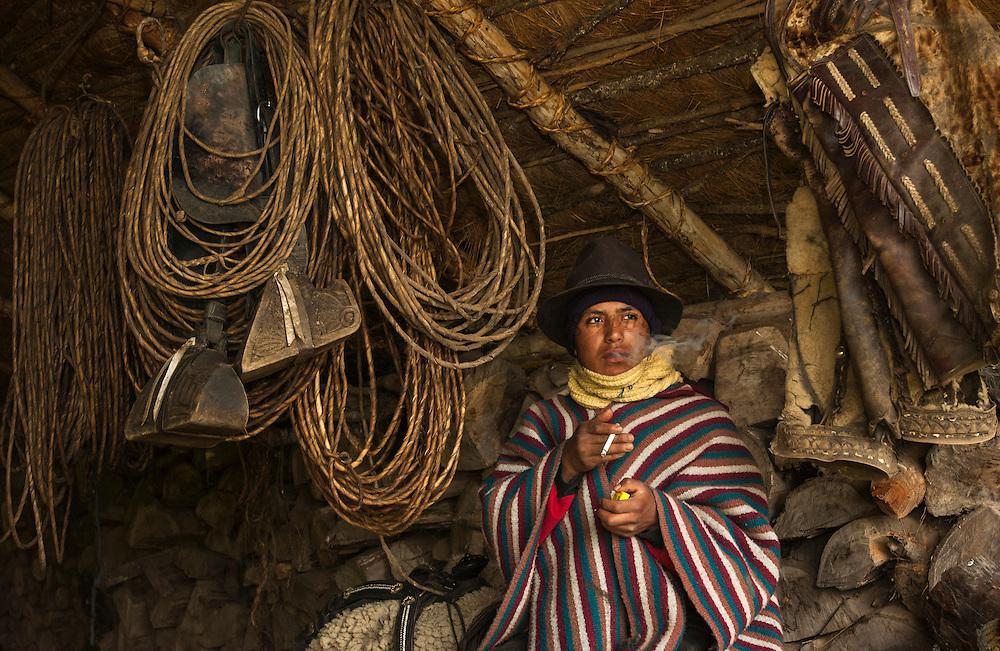 Ecuadorian Chagra (cowboy) in Tack Room<br /> Hacienda del Vallle  (Ranch)<br /> base of Cotopaxi Volcano<br /> Andes<br /> ECUADOR.  South America