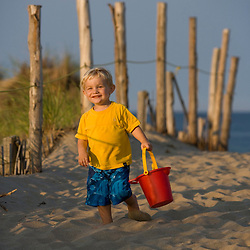 A young boy (age 2)  head to the beach at the Cape Cod National Seashore in Truro, Massachusetts.  Head of the Meadow Beach.