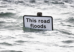 © Licensed to London News Pictures. 01/10/2019. Bosham, UK. A sign says 'This road floods' as high tide covers roads in the village of Bosham in West Sussex. Parts of the South are being affected by the aftermath of Hurricane Lorenzo with numerous flood warnings in place. Photo credit: Peter Macdiarmid/LNP