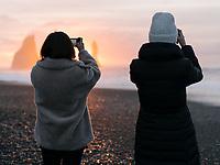 Tourist photographing the sunrise at Reynisfjara black sand beach, South coast of Iceland.