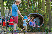 Children and adults enjoy a green sculpture in the Solus area - The 2018 Latitude Festival, Henham Park. Suffolk 14 July 2018