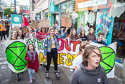 """© Licensed to London News Pictures. 01/09/2019. Manchester, UK. Extinction Rebellion Youth march through the Arndale Shopping Centre and through Manchester after holding a """" die-in"""" in front of fashion retailers River Island and Next . Extinction Rebellion block roads around Deansgate in Manchester City Centre , during a third day of planned disruption organised by environmental campaigners . Manchester City Council has declared a climate emergency but activists say the council's development plans do not reflect this . Photo credit: Joel Goodman/LNP"""