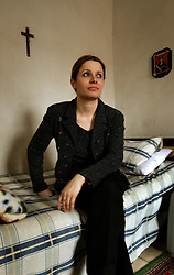 Rita Elias, 30, sits in her bedroom, Baghdad, Iraq, March, 6, 2004. Elias is a former stockbroker who now works for a bank in Baghdad. Her house was partially damaged in the war. In a family of 11 children, Elias has two sisters who live in the United States and a brother-in-law who is an Iraqi-American working as a translator in Iraq for the Department of Defense.