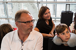 Dutch family Sjored Buren, 51, His partner Petra Kappen, 47 and children Niels, 13, and Inge, 9, travelling back to the Netherlands fro Phoenix, Arizona, await details of alternative flight arrangements at Terminal 5 at Heathrow Airport after an IT glitch brings British Airways systems to a halt, causing disruption to thousands of passengers with flights cancelled and delayed. London, August 07 2019.