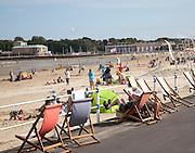 Holidaymakers enjoying sunshine on the sandy beach at Weymouth, Dorset, England, UK