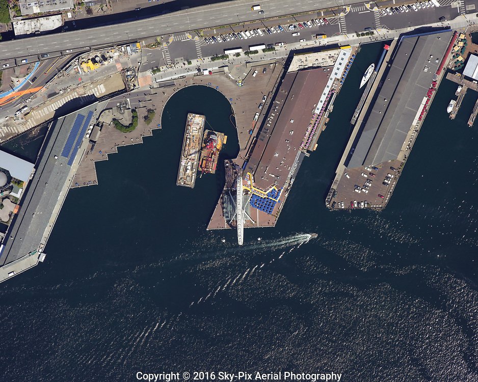 Vertical aerial view looking down on Piers 59, 57, and 56, along the waterfront of Seattle.