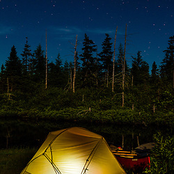 """Tent and canoe next to the Cold Stream """"deadwater"""" above Upper Cold Stream Falls in Maine's Northern Forest. Night. Johnson Mountain Township."""