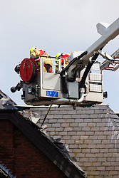 Smoke continues to rise from roof timbers where Firefighters use an aerial platform and remove roofing material to attack the last few pockets of fire at The Mall in Walthamstow in North East London, that broke out during rush hour this morning and appears to have destroyed the foodcourt and according to a manager escorted by LFB officials at the adjacent Asda, a large amount of stock. London, July 22 2019.