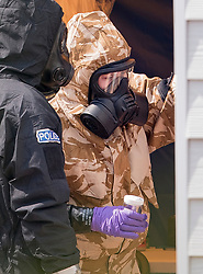 © Licensed to London News Pictures. 06/07/2018. Amesbury, UK. Police in protective suits and gas masks gather evidence at the front door of a house in Muggleton Road in Amesbury where a couple, named locally as Dawn Sturgess, 44, and her partner Charlie Rowley, 45, were taken ill on Saturday 30th June 2018. Police have confirmed that the couple have been in contact with Novichok nerve agent. Former Russian spy Sergei Skripal and his daughter Yulia were poisoned with Novichok nerve agent in nearby Salisbury in March 2018. Photo credit: Peter Macdiarmid/LNP