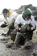 Volunteers clean up Insuela beach on December, 30th 2002, in Galicia. Hundreds of volunteers cleaned up Galicia coastline for months after the disaster. The Prestige oil spill happened off the coast of Galicia caused by an oil tanker sinking in 2002. The spill polluted thousands of kilometers of coastline and more than one thousand beaches on the Galician, Portuguese, Spanish, Basque and French coast, as well as it caused great harm to the local fishing industry. (Ander Gillenea / Bostok Photo)