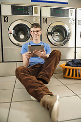 Young man using digital tablet in laundry, smiling