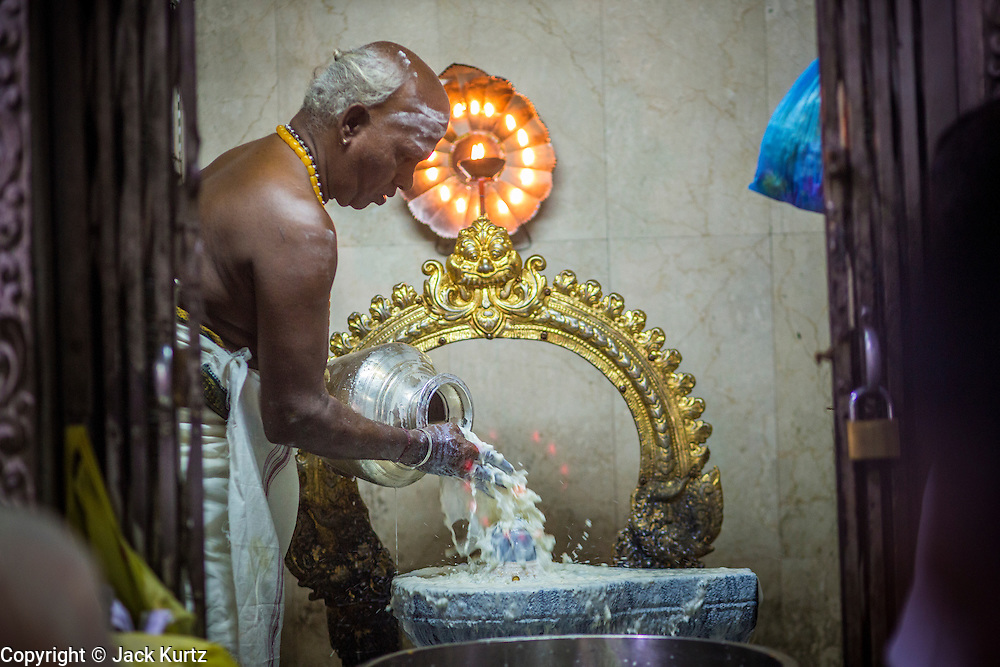 22 DECEMBER 2012 - SINGAPORE, SINGAPORE:  A Hindu priest bathes deities in milk during prayers at Sri Veeramakaliamman Temple, a Hindu temple located in Little India in Singapore. The Sri Veeramakaliamman Temple is dedicated to the Hindu goddess Kali, fierce embodiment of Shakti and the god Shiva's wife, Parvati. Kali has always been popular in Bengal, the birthplace of the labourers who built this temple in 1881. Images of Kali within the temple show her wearing a garland of skulls and ripping out the insides of her victims, and Kali sharing more peaceful family moments with her sons Ganesha and Murugan. The building is constructed in the style of South Indian Tamil temples common in Tamil Nadu as opposed to the style of Northeastern Indian Kali temples in Bengal.      PHOTO BY JACK KURTZ