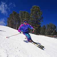 Skiers cruise down a run at Red Lodge Mountain, Montana.