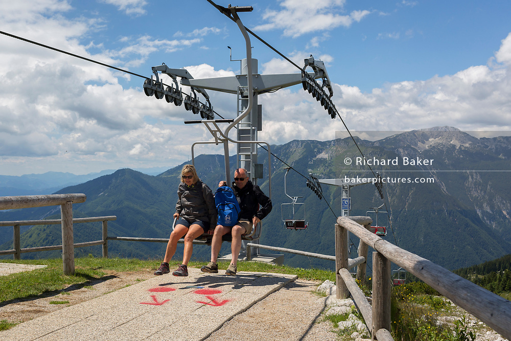 Passengers prepare to leave the chairlift in Velika Planina, on 26th June 2018, in Velika Planina, near Kamnik, Slovenia. Velika Planina is a mountain plateau in the Kamnik–Savinja Alps - a 5.8 square kilometres area 1,500 metres (4,900 feet) above sea level. Otherwise known as The Big Pasture Plateau, Velika Planina is a winter skiing destination and hiking route in summer. The herders' huts became popular in the early 1930s as holiday cabins (known as bajtarstvo) but these were were destroyed by the Germans during WW2 and rebuilt right afterwards by Vlasto Kopac in the summer of 1945.