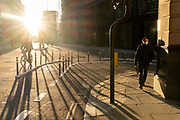 With most Londoners still working from home, a commuter walks and a cyclist passes around the widened corner of Threadneedle and Old Board Streets at evening rush-hour during the third lockdown of the Coronavirus in the City of London, the capitals financial district, on 26th February 2021, in London, England.