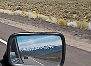 classic Mini Cooper in the rear view mirror of a classic Mini Cooper along US 50 in Nevada with the Toiyabe Peak Range in the background of the mirror reflection and sagebrush desert along the highway around the mirror.