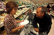 (MODEL RELEASED IMAGE). Deb and Mark discuss their grocery list for one weeks' worth of food, while their son Tadd watches over the second grocery cart behind. (Supporting image from the project Hungry Planet: What the World Eats.)