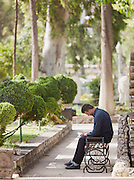 A man sits in the grounds of the Naional Museum in Damascus, Syria
