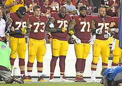 """From left to right: Washington Redskins offensive tackle Ty Nsekhe (79), center Chase Roullier (73), offensive tackle Morgan Moses (76), offensive tackle Trent Williams (71), and offensive guard Brandon Scherff (75) lock arms in solidarity as the national anthem is sung prior to the game against the Oakland Raiders at FedEx Field in Landover, Maryland on Sunday, September 24, 2017. The Redskins chose to demonstrate prior to their nationally televised contest following tweets earlier in the day from United States President Donald J. Trump urging owners to """"fire or suspend"""" players who participated in the protests by not standing for the anthem. Photo by Ron Sachs/CNP/ABACAPRESS.COM"""