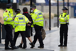 © Licensed to London News Pictures. 25/07/2020. London, UK. Police arrest an Extinction Rebellion activist who locked herself to a drilling rig in the Thames close to the 02 Arena in Greenwich this morning . The rig is involved with preparatory drilling for the Silvertown Tunnel which is planned to connect the Greenwich Peninsula with west Silvertown. Extinction Rebellion oppose the building of the tunnel due to the increase in air pollution it may cause. Photo credit: George Cracknell Wright/LNP