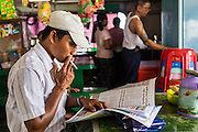 17 JUNE 2013 - YANGON, MYANMAR: A man reads a newspaper on the Yangon-Dala cross river ferry. The Burmese newspaper industry has enjoyed explosive growth this year after private ownership was allowed in 2013. Private newspapers were shut down under former Burmese leader Ne Win in the early 1960s. The revitalized private press is a sign of the dramatic changes sweeping Myanmar, formerly Burma, in the last three years.      PHOTO BY JACK KURTZ