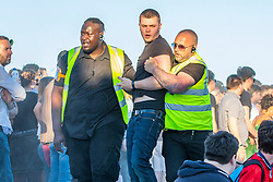 © Licensed to London News Pictures. 28/06/2018. Brighton, UK. England supporters are forcibly removed from the venue due to disuptive behaviour. England fans watch the the World Cup match between England and Belgium, on Brighton beach on the south coast of England. Photo credit: Hugo Michiels/LNP