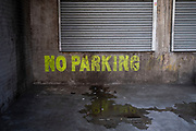 No parking sign painted on a wall near shutters to prevent illegal parking on private property in the city centre on 30th March 2021 in Birmingham, United Kingdom.