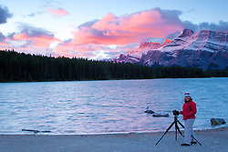 A Canadian autumn sunrise lights up Mt Rundell, showering it with alpenglow, over Two Jack Lake as, happy photographer, Diana captures the magic in Banff National Park.