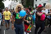 Man wearing a blonde wig. Notting Hill Carnival in West London. A celebration of West Indian / Caribbean culture and Europe's largest street party, festival and parade. Revellers come in their hundreds of thousands to have fun, dance, drink and let go in the brilliant atmosphere. It is led by members of the West Indian / Caribbrean community, particularly the Trinidadian and Tobagonian British population, many of whom have lived in the area since the 1950s. The carnival has attracted up to 2 million people in the past and centres around a parade of floats, dancers and sound systems.