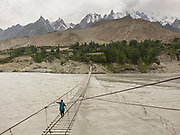 Trekking across the a suspension bridge, over the Hunza river.