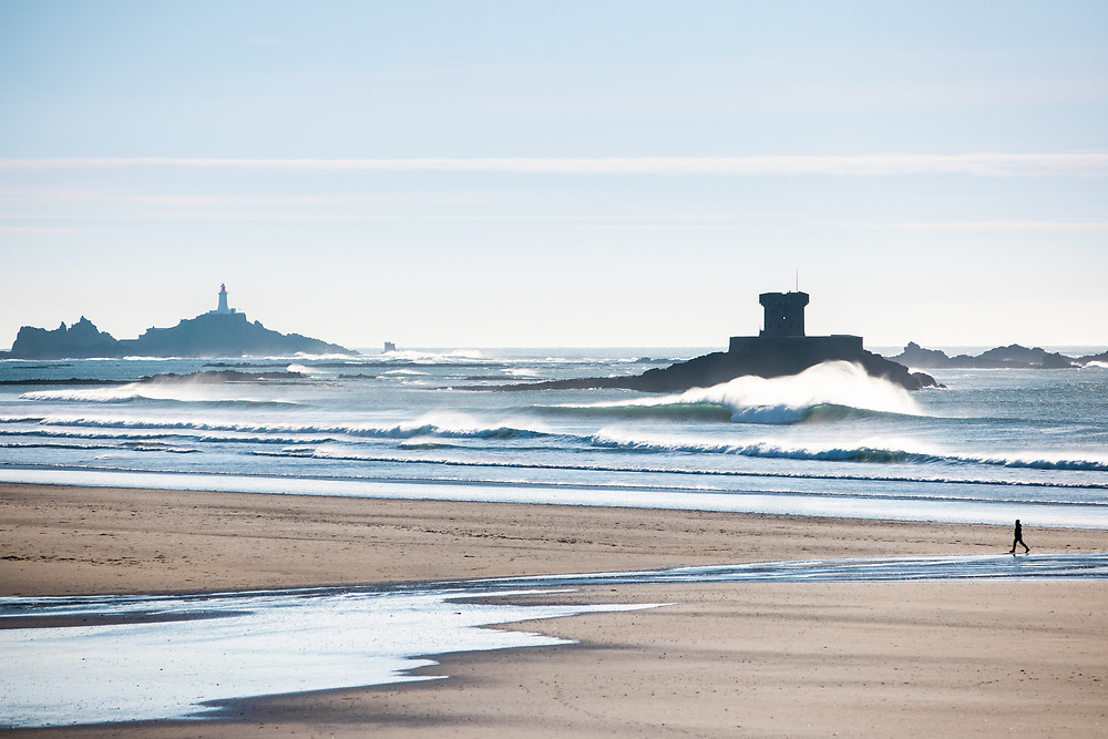 Waves breaking in front of La Rocco Tower, St Ouen's Bay, Jersey, with views to Corbiere lighthouse beyond on a sunny winter afternoon